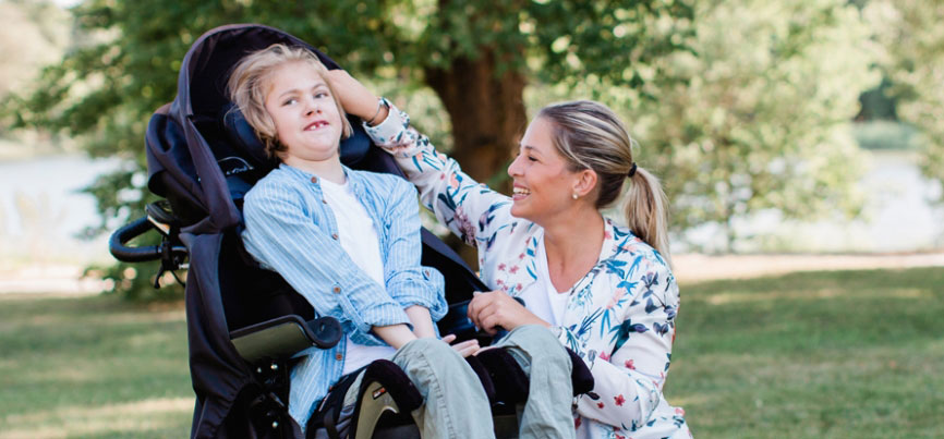 barn i rullstoll tillsammans med personlig assistent