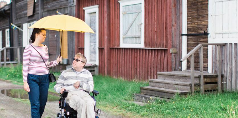 Man i rullstol där personlig assistent håller paraply